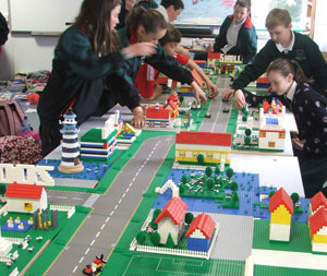 Cheering Classroom of Children around their Lego Town Building Project